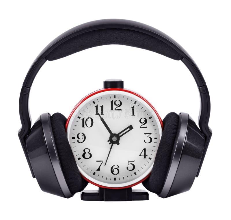 Les écouteurs, ont mis dessus une horloge ronde photographie stock