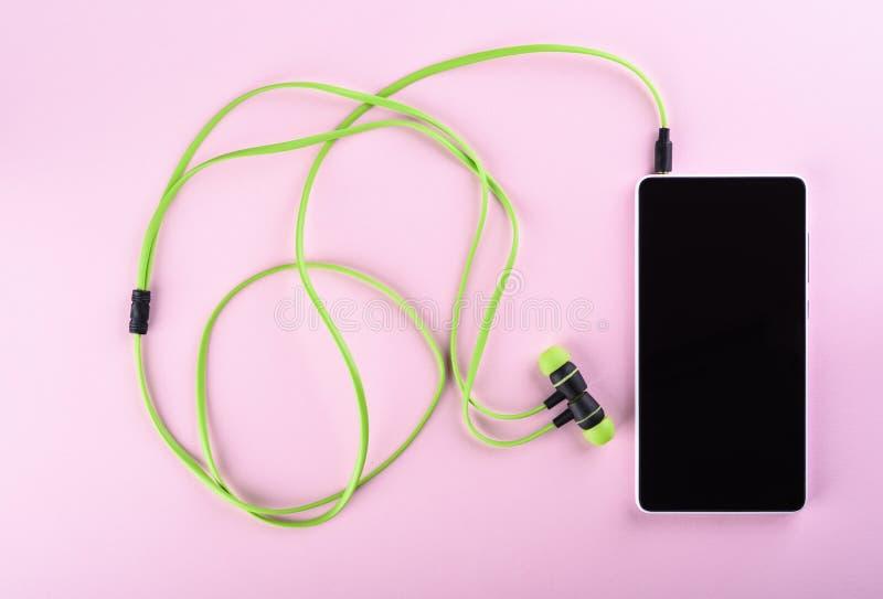 Les écouteurs verts se sont reliés à un smartphone d'isolement sur un fond rose Accessoires pour écouter individuel les dossiers  photos stock