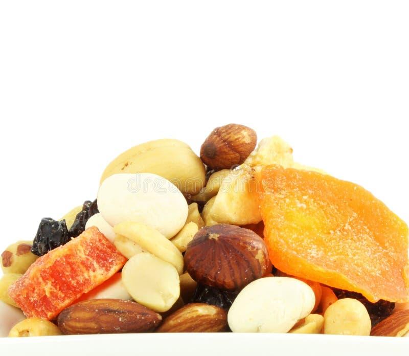 Les écrous secs mélangés de fruits traînent le plan rapproché de mélange à l'arrière-plan blanc images stock