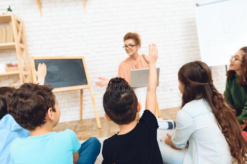 Les élèves tire des mains à la question du ` s de professeur de réponse en verres à l'école primaire photographie stock