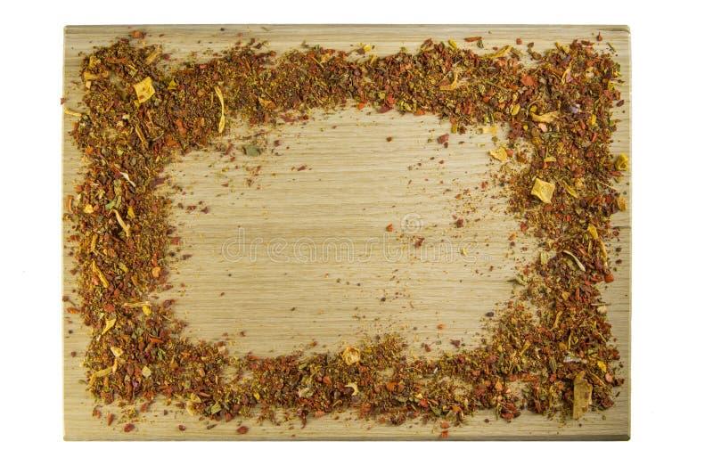 Les épices d'assaisonnements ont dispersé sur une planche à découper sous forme de cadre photographie stock libre de droits
