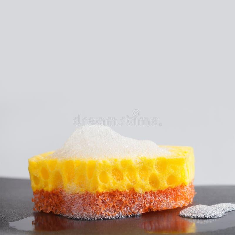 Les éponges colorées avec des lessives de savon écument sur le fond noir concept d'alimentations stabilisées Copiez l'espace, mac photographie stock libre de droits