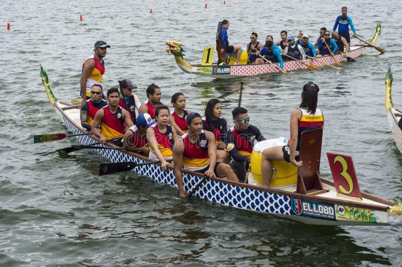 Les équipes de concurrence de personnes s'embarquent sur les bateaux indigènes de tête de dragon de rangée de sports pendant le D images stock