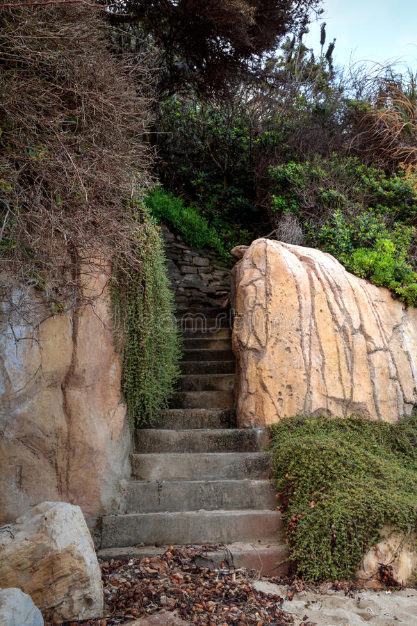 Les étapes de pierre menant dans une alcôve ont trouvé sur une plage de la Californie photo libre de droits