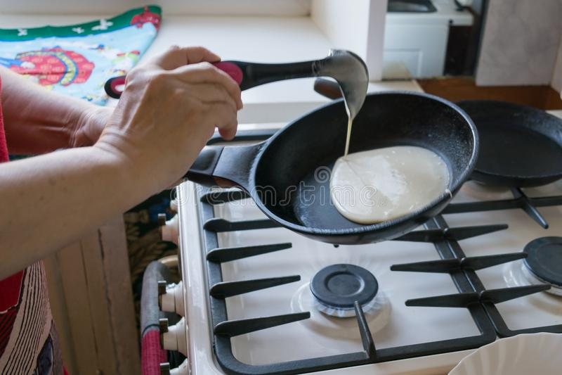 Les étendre de la pâte dans une casserole pour les crêpes de cuisson dans les mains d'une fin de femme agée  photographie stock libre de droits