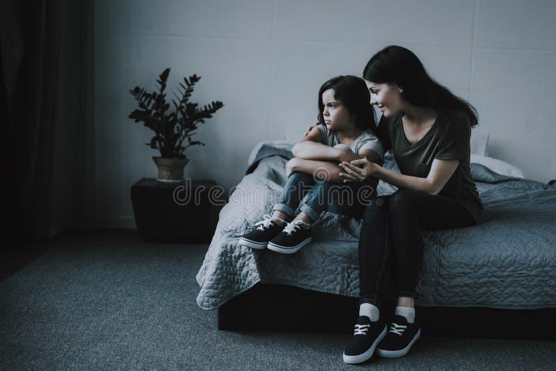 Les étreintes de mère calme la fille bouleversée dans la chambre à coucher photo stock