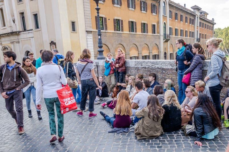 Les étudiants écoutent une leçon historique de conférence de son professeur reposant dans la rue sur le trottoir du pont Fabricio photos libres de droits