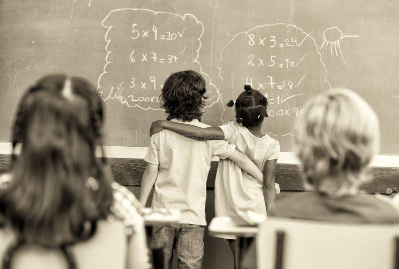 Les étudiants élémentaires ethniques multi ont embrassé apprendre des maths à la craie photos libres de droits