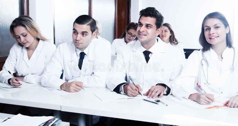 Les étudiants dans des manteaux blancs écoutent la conférence photographie stock