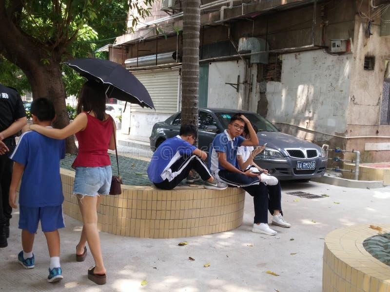 Les étudiants de collège jouent des téléphones portables en dehors du campus image libre de droits