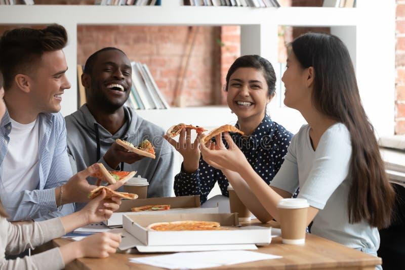 Les étudiants divers comblés rient ayant la coupure appréciant la pizza photographie stock libre de droits