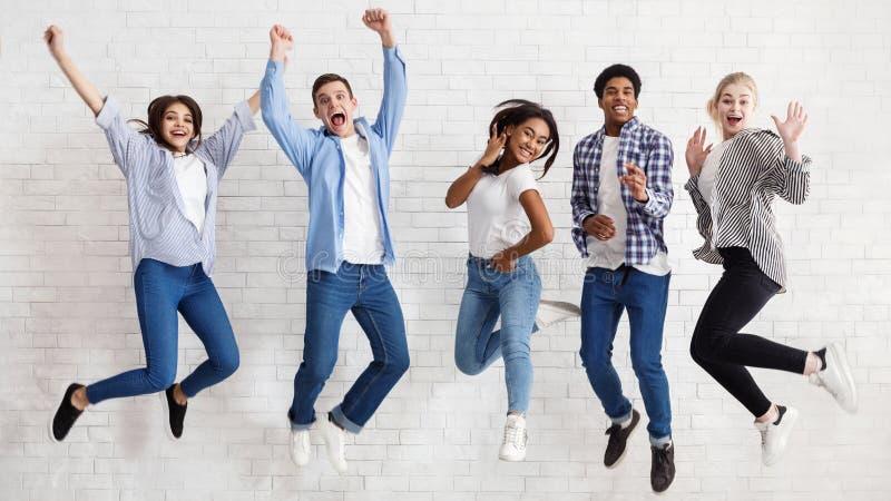 Les étudiants heureux sautant sur le fond blanc, ont passé des examens photos libres de droits