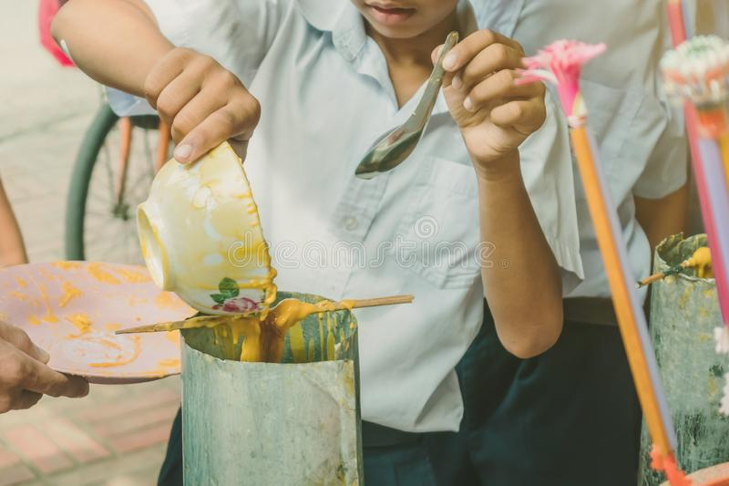 Les étudiants joignent l'offre moulée de fonte de bougie au temple pour Lent Day bouddhiste, photographie stock