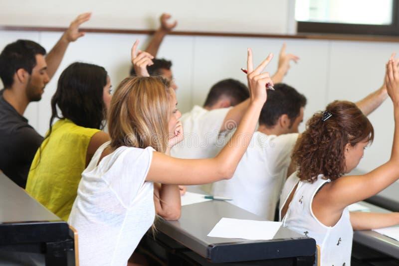 Les étudiants ont mis la main dans la chambre de classe image libre de droits