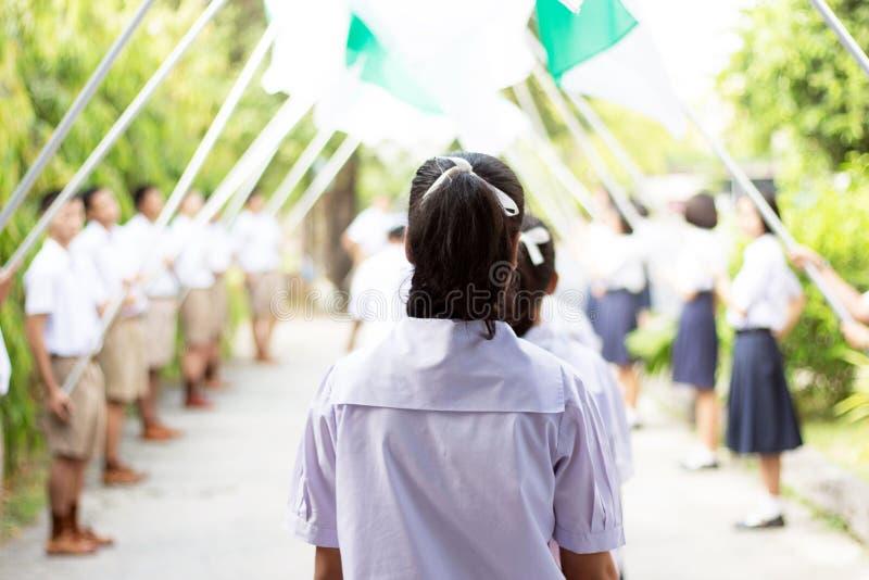 Les étudiants passent le drapeau de l'honneur le jour  photos stock