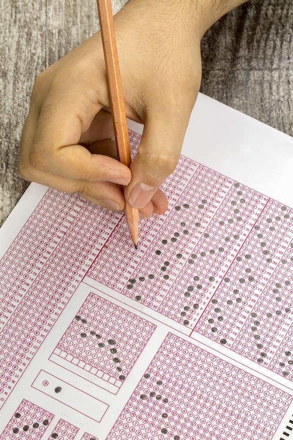 Les étudiants remettent faire le jeu-concours d'examens le papier réactif photographie stock