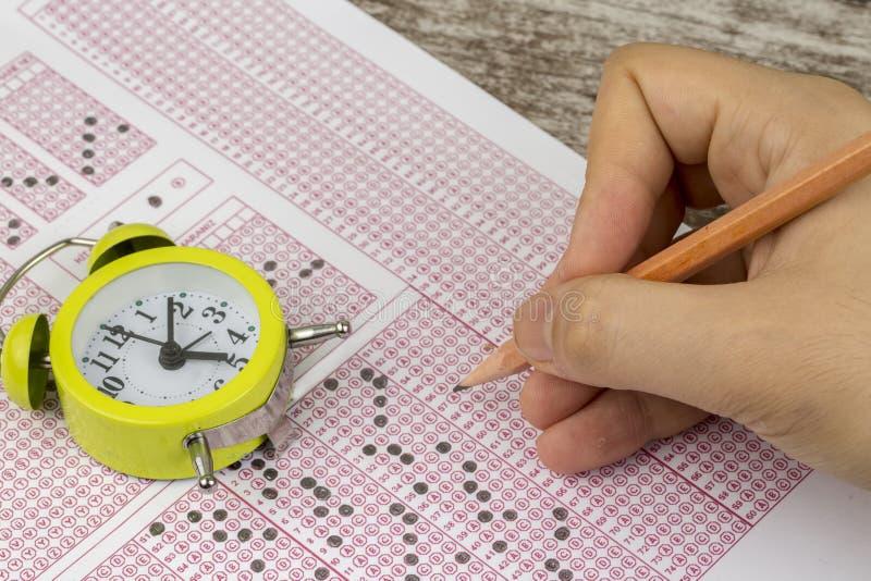 Les étudiants remettent faire le jeu-concours d'examens le papier réactif images stock