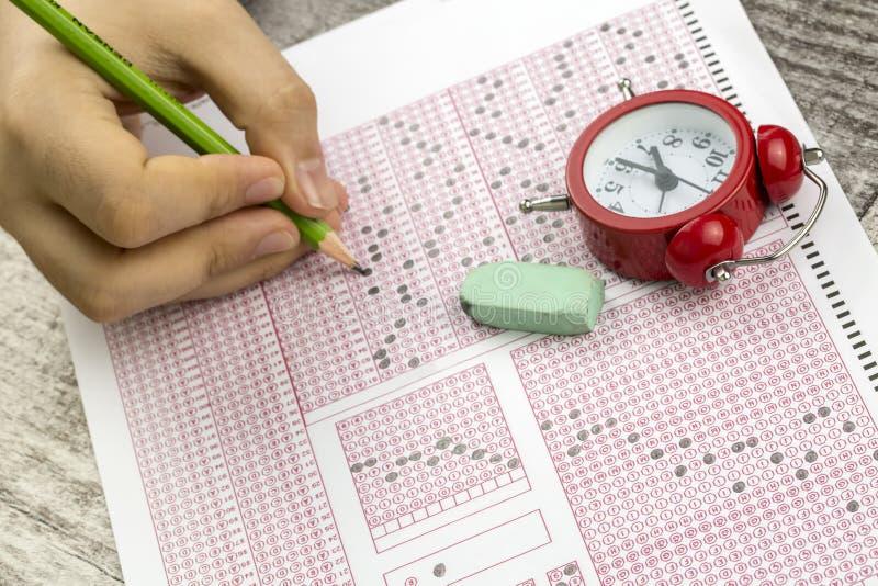 Les étudiants remettent faire le jeu-concours d'examens le papier réactif image libre de droits