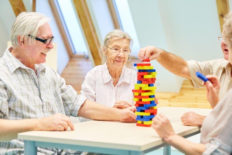 Les aînés construisent une tour des blocs constitutifs image stock