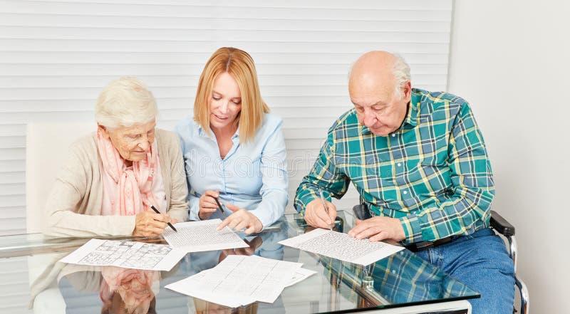 Les aînés et la jeune femme résolvent des puzzles ensemble photos stock