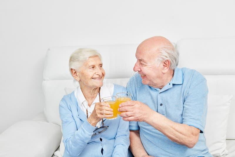 Les aînés heureux couplent le grillage avec le jus d'orange images stock