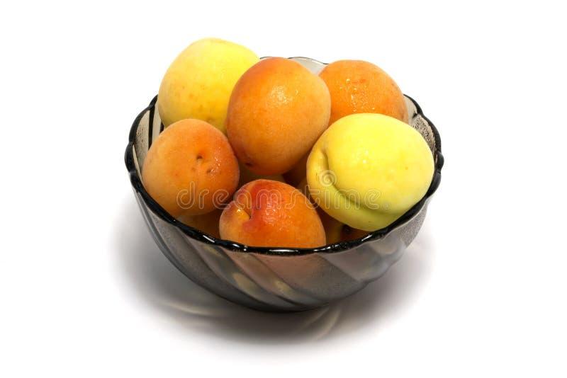 Les abricots avec de l'eau se laisse tomber dans le bol en verre sur le fond blanc photographie stock libre de droits