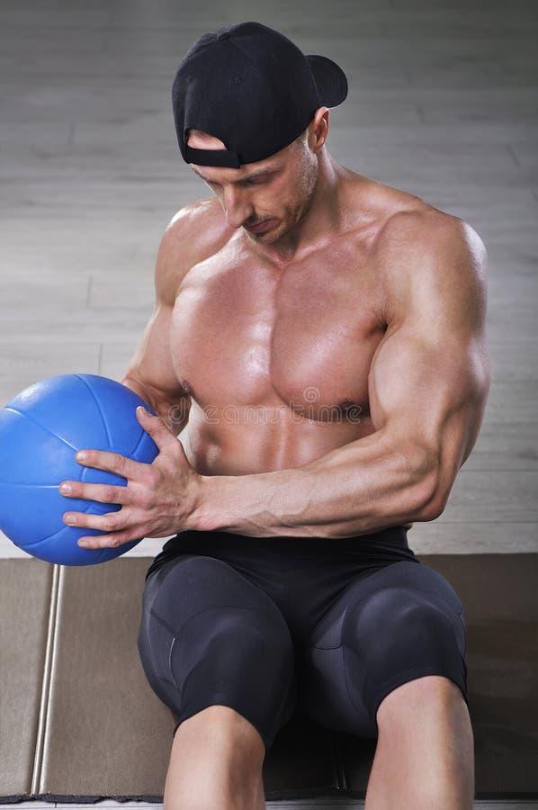Les ABS de exécution d'homme sportif puissant bel s'exercent avec le medicine-ball photo stock