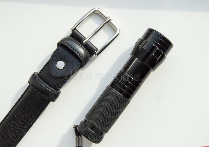 Les accessoires bracelet en cuir noir et lampe-torche des hommes d'isolement sur le fond blanc image libre de droits