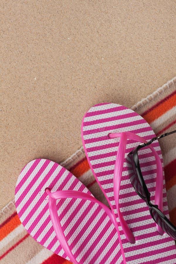 Les accessoires d'été les bascules électroniques et la serviette Fond de texture de plage de sable images stock