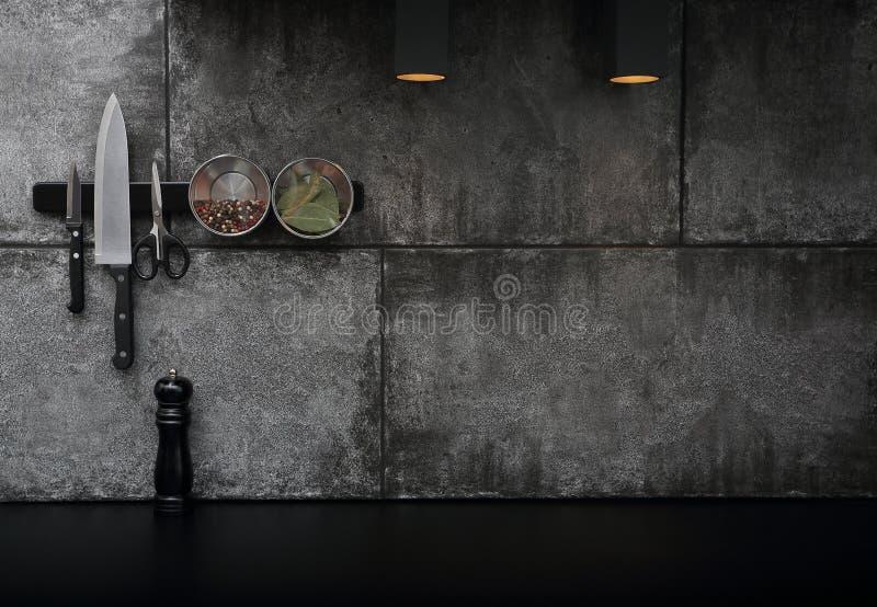 Les accessoires de cuisine ont monté sur le mur en pierre noir photos stock