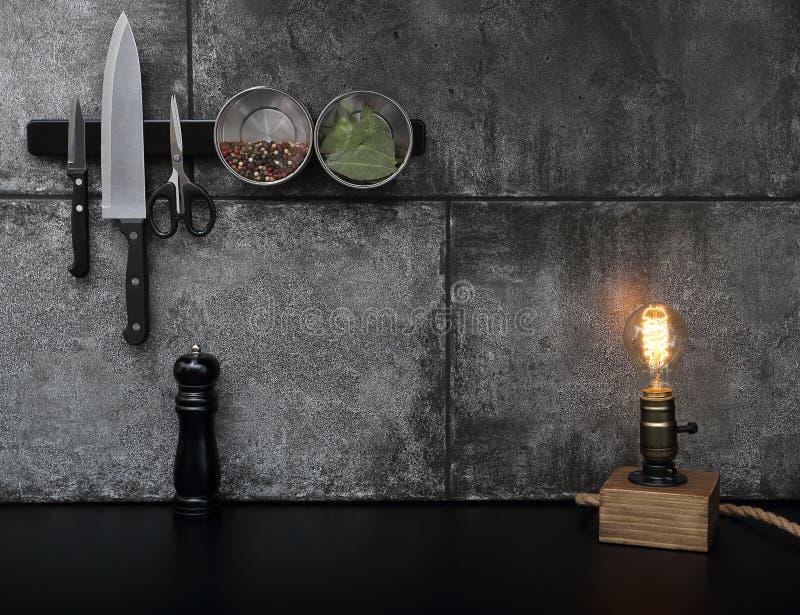 Les accessoires de cuisine ont monté sur le mur en pierre noir images stock