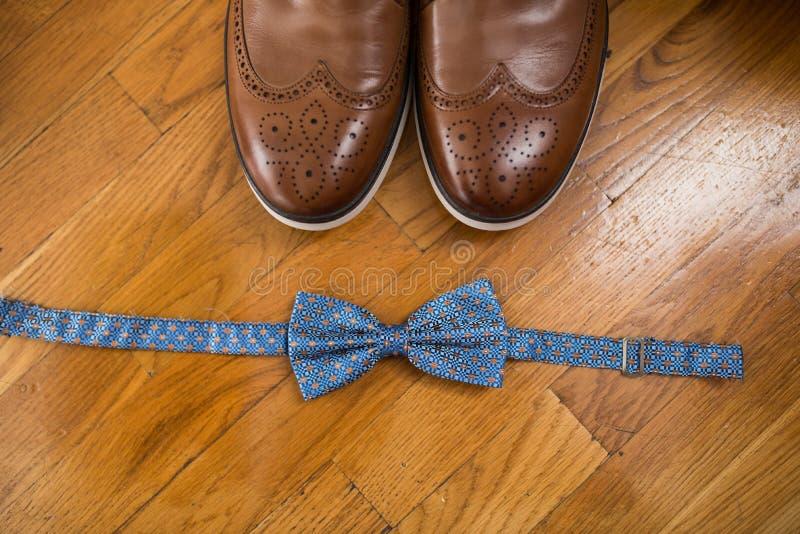 Les accessoires du ` s de marié Noeud papillon bleu et une pièce de chaussures en cuir brunes sur un fond en bois image libre de droits