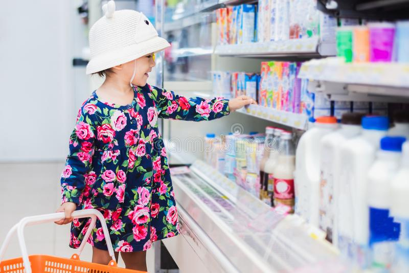 Les achats asiatiques doux de fille dans le mini marché avec le panier, ont plaisir à acheter la chose image libre de droits