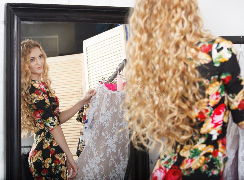 Robes d'achats de femme regardant dans le miroir images libres de droits