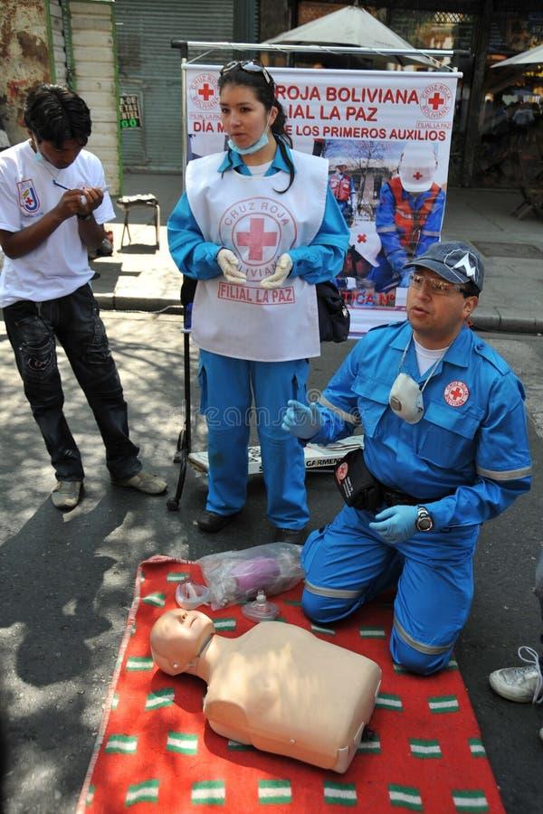 Les activistes de la Croix-Rouge enseignent des premiers secours de personnes sur une rue de ville photos stock