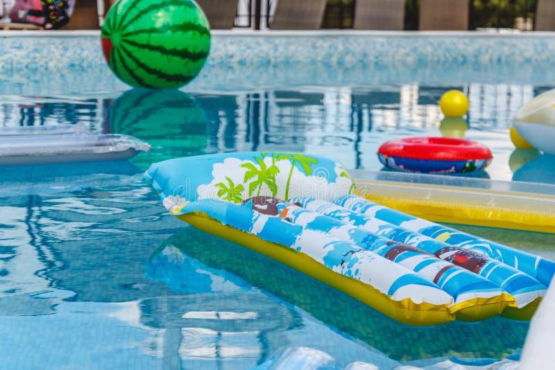 Les activités de l'eau gonflables, boules, matelas, cercles, tubes flottent sur l'eau dans la piscine image libre de droits