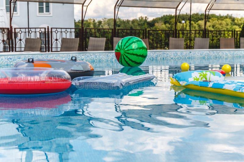 Les activit?s de l'eau gonflables, boules, matelas, cercles, tubes flottent sur l'eau dans la piscine image libre de droits