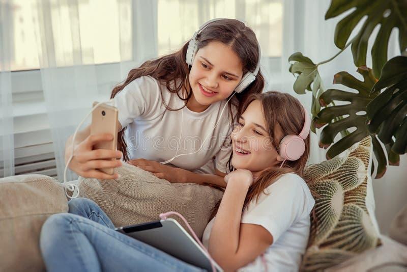 Les adolescentes avec l'ordinateur de PC de comprimé et la musique de écoute d'écouteurs et communiquent dans les réseaux sociaux photos stock