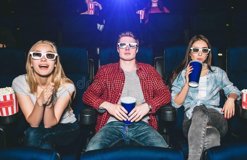 Les adolescents émotifs s'asseyent dans les chaises et le film de observation La fille blonde l'observe avec enthousiasme cuir de images stock