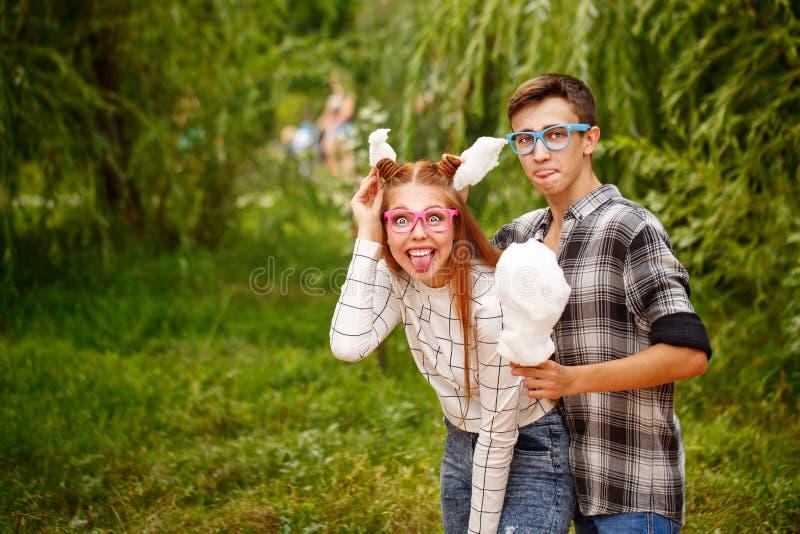 Les adolescents affectueux de couples mangent la sucrerie de coton photos stock