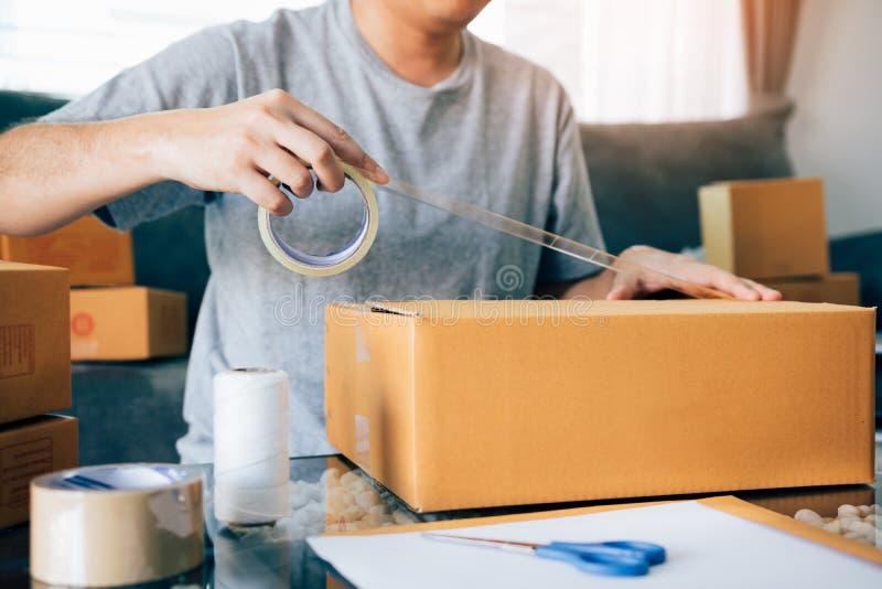 Les adolescents asiatiques d'entrepreneur utilisent la bande pour sceller la boîte en emballant le produit pour envoyer aux clien images libres de droits