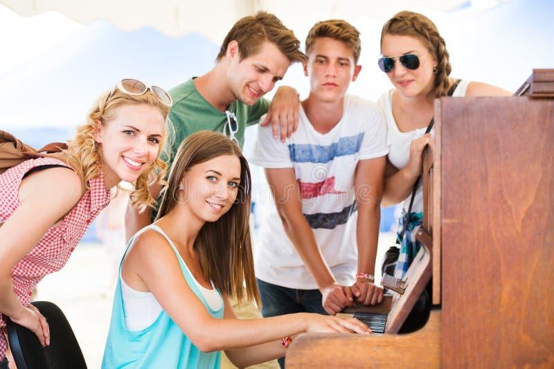 Les adolescents au festival de musique d'été, fille joue le piano photos libres de droits