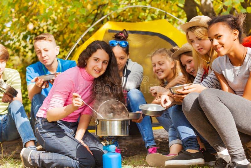 Les adolescents font cuire la soupe dans le pot métallique pendant le camping images libres de droits