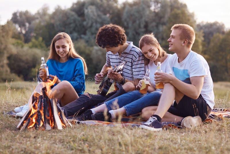 Les adolescents joyeux s'asseyent étroitement entre eux sur le feu proche au sol, ont le pique-nique ensemble, jouent la guitare  images libres de droits