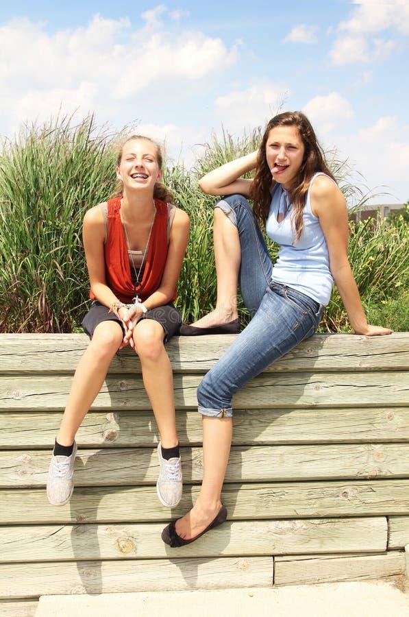 Les adolescents s'asseyent à l'extérieur images stock