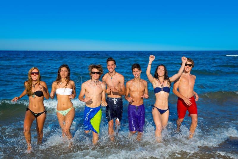 Les ados groupent l'éclaboussement heureux courant sur la plage photographie stock libre de droits