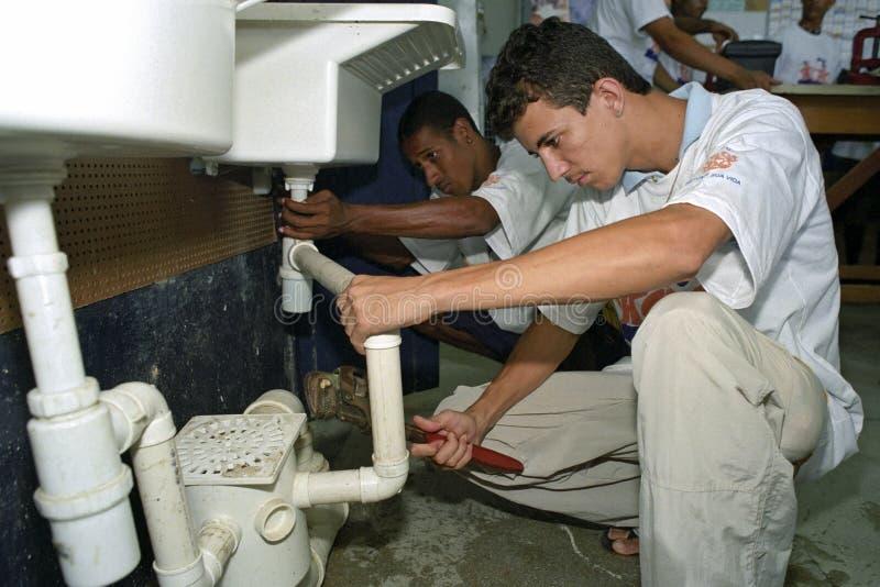 Les ados latins apprennent la profession de la tuyauterie, école commerciale image libre de droits