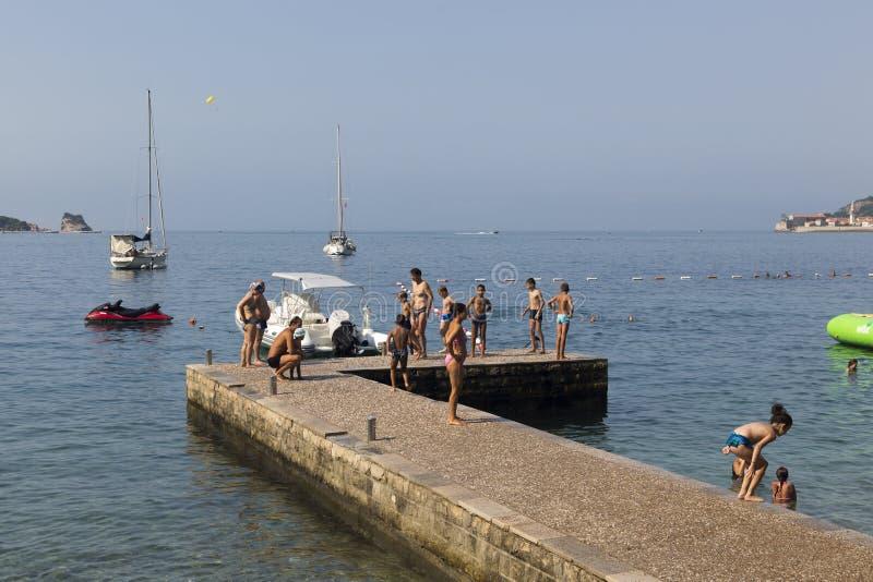 Les adultes et les enfants nagent et se reposent sur le pilier de la plage de ville images stock