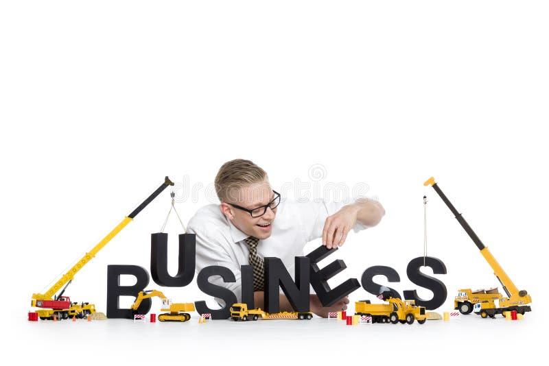 Les affaires commencent vers le haut : Affaire-mot de bâtiment d'homme d'affaires. photos stock