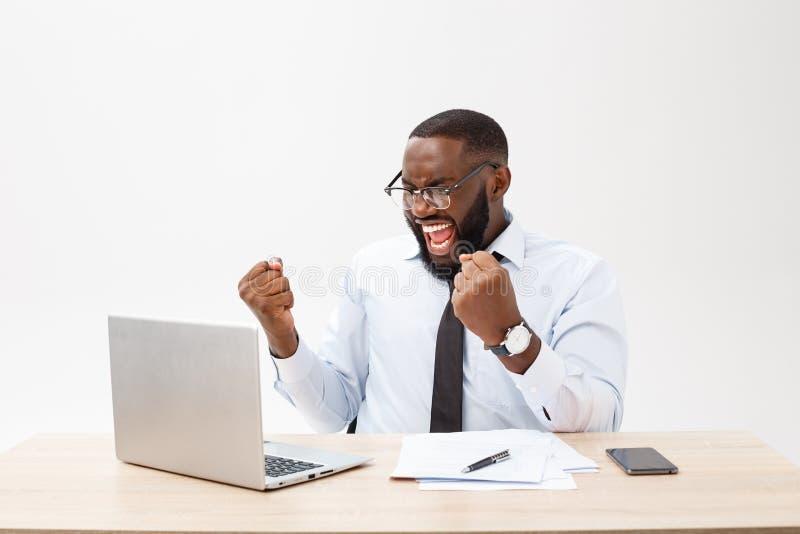 Les affaires sont sa vie Jeune homme africain gai le tenue de soirée et en travaillant sur l'ordinateur portable images libres de droits